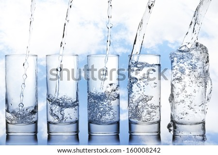 stages of pouring water into a glass - stock photo