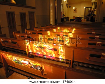 stained glass light casts onto church pews. - stock photo