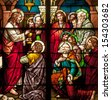 Stained glass window depicting Bible story of Last Supper with Jesus instituting the Holy Eucharist - stock photo