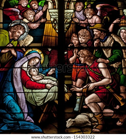 Stained glass window depicting biblical Christmas scene, the birth of Jesus Christ - stock photo