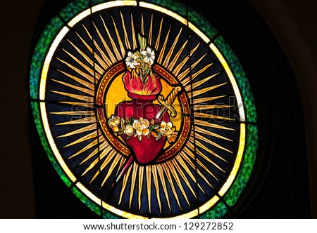 Stained glass window depicting Catholic devotion of Immaculate Heart of Mary pierced by a sword - stock photo