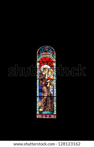 Stained glass window depicting St. Anthony of Padua and Lisbon with the baby Jesus in his arms constant in the Romanesque cathedral of Porto, Portugal - stock photo