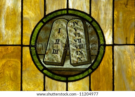 Stained glass window in a medieval church showing the 10 commandment tablets - stock photo