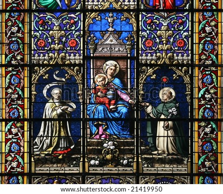 Stained glass window in St.Sulpice church ( Fougeres, France), having in its center Virgin Mary and Holy Child Jesus.