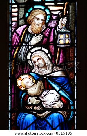 Stained glass window, in 19th century (built in 1859) church, of baby Jesus, Mary, and Joseph in the manger.