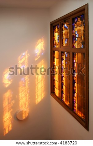 Stained glass window with the sun coming through.