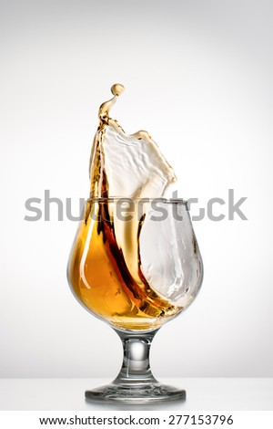 Staing splahing glass  on light background - stock photo