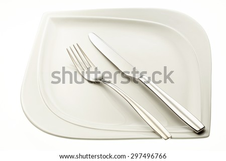 Stainless fork and knife on plate isolated on white background