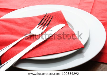 stainless fork knife and plate set on a table