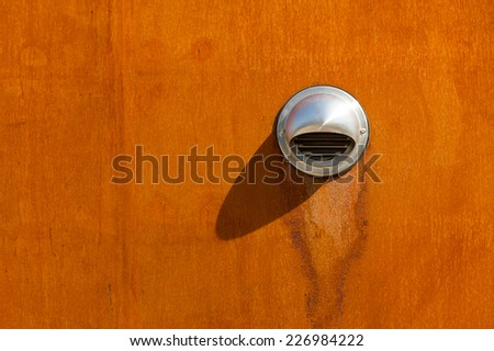 Stainless steel air vent on a rusted, steel wall. - stock photo
