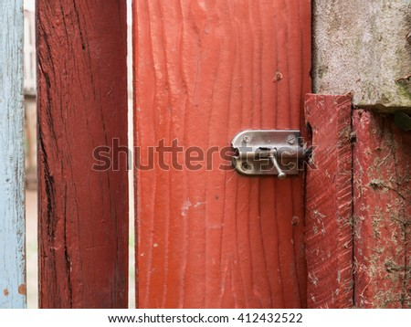 Stainless steel bolt on the red wooden door, selective focus on bolt - stock photo