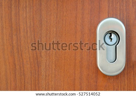 Stainless steel door lock and a Keyhole on the wooden door