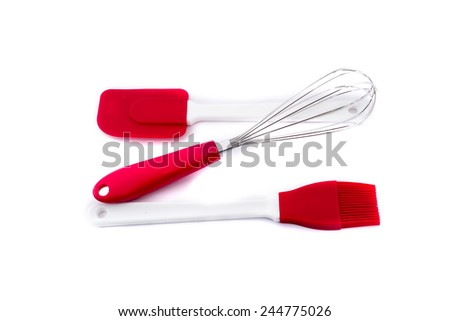 Stainless steel egg whisk in red, silicone spatula in red and silicone pastry brush in red isolated on white background - stock photo