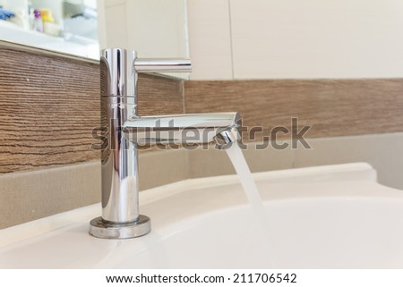 Stainless Steel Faucet with flowing water - stock photo
