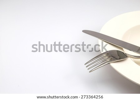 Stainless steel fork and knife on a white plate isolated on white background - stock photo
