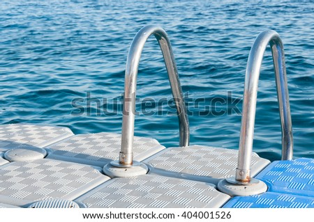 Stainless steel hand rails of a swimmers' boarding ladder, mounted on the edge of a plastic, floating dock in a tropical sea.