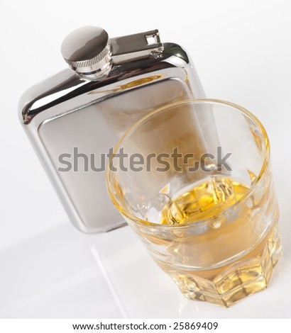 Stainless steel hip flask and glass of whisky