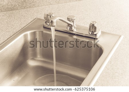 stainless steel kitchen sink and faucet on a yellow granite worktop decoration water flowing from - American Kitchen Sink
