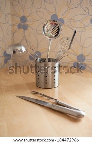 stainless steel kitchen tools  equipment on background of wooden table - stock photo