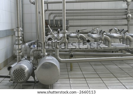 stainless steel pipes and valves in modern dairy - stock photo