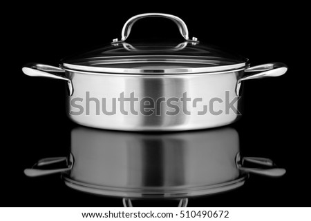 Stainless steel pot on a shiny black surface.