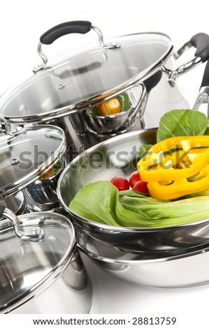 Stainless steel pots and pans isolated on white background with vegetables - stock photo
