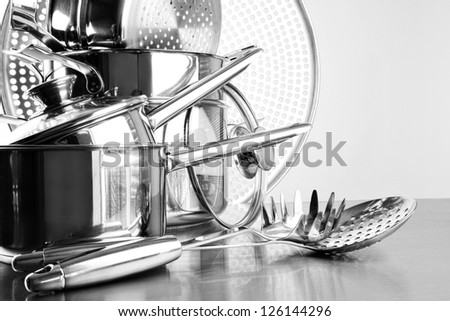 Stainless steel pots and utensils on table counter - stock photo