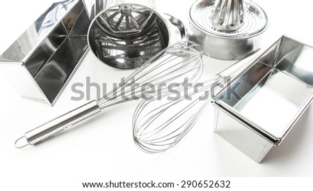 Stainless steel set of eggbeater, sifter flour siever, baking mould container and juice presser. Concept of tools for cake making. Slightly defocused and close up shot. Copy space. - stock photo