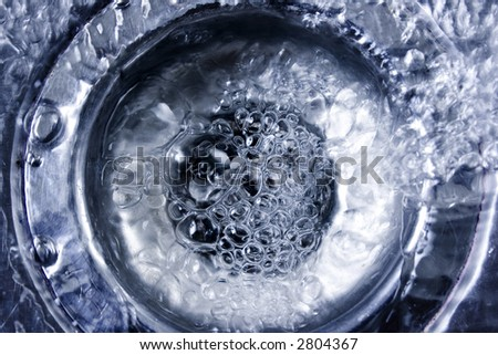 Stainless steel sink drain with running water and bubbles - stock photo