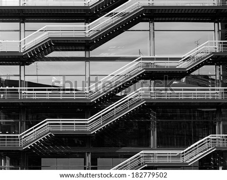 Stainless steel staircase against a glass wall in a modern building in Madrid, Spain. Black and white, high contrast. - stock photo