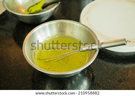 Stainless steel whisk in green cream of sweet cake