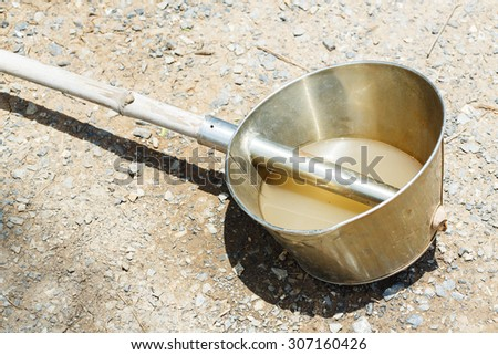 Stainless water ladle with bamboo shaft handle, agricultural tool - stock photo