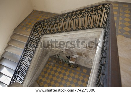 staircase in an old villa (european, france, looking down at a bicycle perked in the hallway) - stock photo