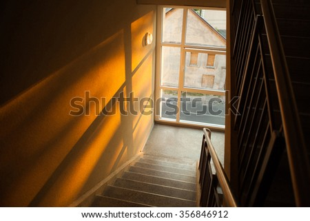 Staircase of apartment building with sunset light playing on the wall - stock photo