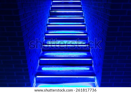 stairs in blue neon lights going up to club or disco.  - stock photo