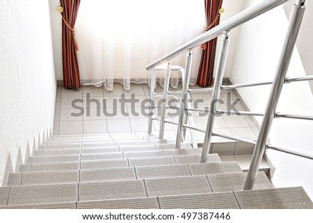 Stairs of ceramic tiles with metal handrail. Windows with curtains morning light blur background