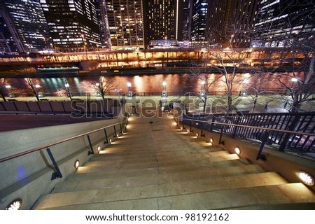 Stairs to Riverwalk in Chicago, IL USA. Chicago River and Skyscrapers at Night. Horizontal Wide Angle Photography. - stock photo