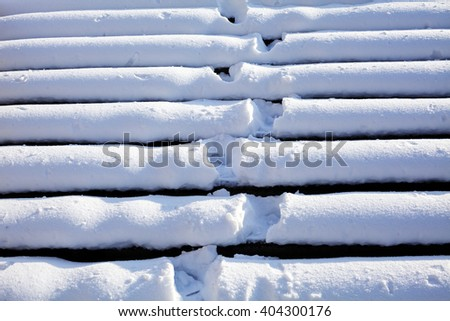 Stairs under heavy snow with footprints - stock photo