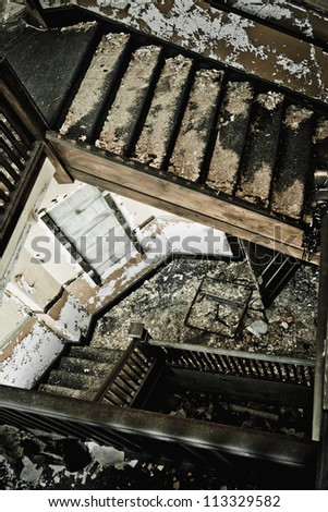 Stairway in an abandoned building, looking down the stairs. - stock photo