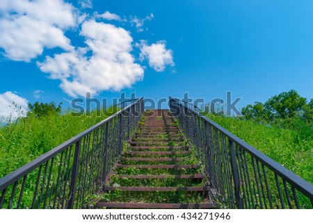 Stairway to heaven. Stairs among grass to blue sky. - stock photo