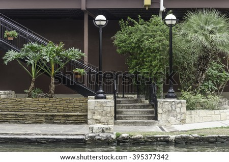 Stairway with cast-iron railings by landscaped area along the River Walk in downtown San Antonio, Texas, USA, for urban, travel, or architectural themes - stock photo