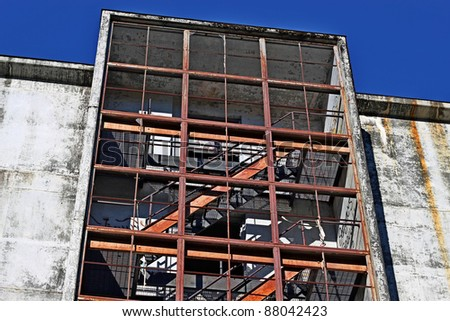 Stairwell of an abandoned cement apartment building with a bright blue sky.