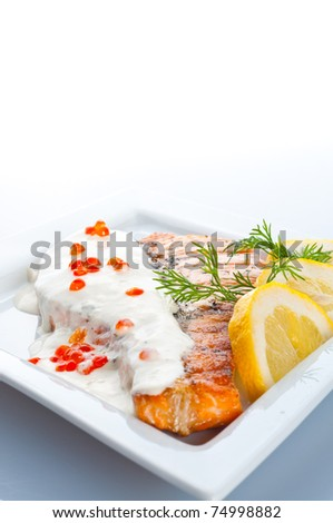 Stake from a salmon with creamy sauce and caviar