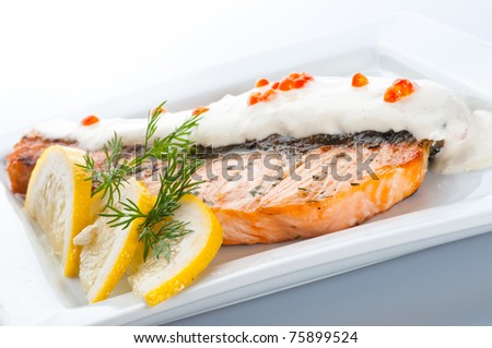 Stake from a salmon with creamy sauce and caviar - stock photo