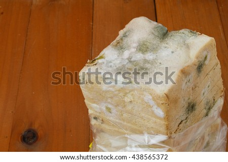 stale white bread on wooden background - stock photo