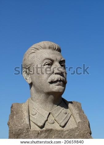 Stalin's sculpture portrait against blue sky - stock photo