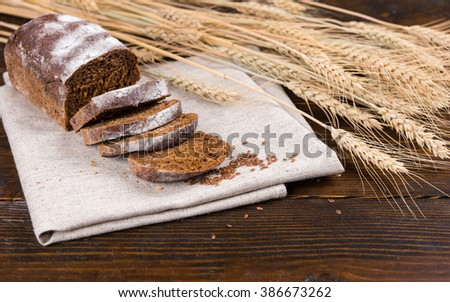Stalks of dried whole wheat stalks and grains next to single loaf of delicious rye bread with slices on brown cloth over dark wooden table - stock photo