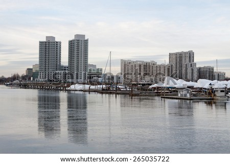Stamford, CT, USA - March 13th, 2015: Daylight view of a marina with boats and buildings in the background in Stamford Connecticut on March 13th, 2015, during the winter season  - stock photo