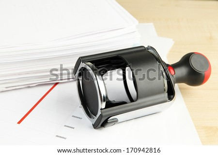 Stamp with papers on table - stock photo