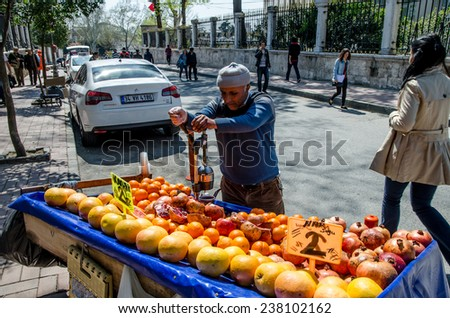 STANBUL - March 31:Vendor sells pomegranate juice on street during Lesser Bairam at Sultanahmet on March 31, 2014 in Istanbul, Turkey.  - stock photo